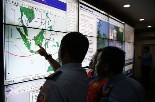 Military and rescue authorities monitor progress in search for AirAsia Flight QZ8501 in Mission Control Center inside National Search and Rescue Agency in Jakarta